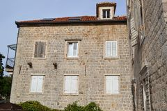 Facade of a multi-storey old stone house. The windows are covered with wooden shutters. Old Town of Budva. Montenegro.  Royalty Free Stock Images