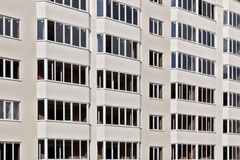The facade of a multi-storey residential building. The windows on the facade of the apartment building stock photo