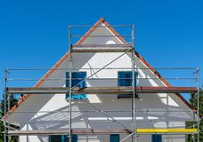 Facade of a new built house with scaffolding at the outisde stock photography