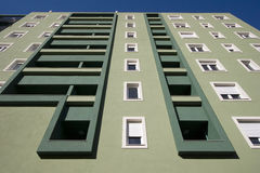 Light and dark green facade with balconies and white windows Stock Image