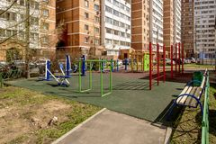 The facade of a new multi-storey apartment building and a children`s playground in Moscow. Panoramic view of residential multi-storey buildings in Moscow with stock photography