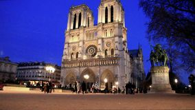 Cathedral of Notre Dame in Paris. Facade of Notre Dame cathedral in Paris next to the Seine River at night stock video