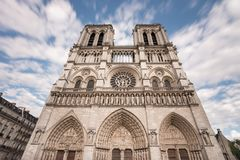 Facade of Notre-Dame de Paris, famous ancient catholic cathedral on a cloudy day. Touristic historical and architectural. Landmark in France. Religion, tourism Royalty Free Stock Photography