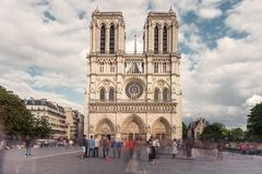 Facade of Notre-Dame de Paris, famous ancient catholic cathedral on a cloudy day. Touristic historical and architectural. Landmark in France. Religion, tourism Stock Images