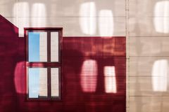 Free Facade Of A Red-yellow Building With Reflections From The Windows Of The Neighboring Building. The Single Window Reflects The Corn Stock Photography - 161762362