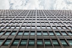 Office Building Shot From The Bottom Up. The Facade Of The Office Building Shot From The Bottom Up With A Horizontal Strip Of Gray Sky With Clouds. The Windows royalty free stock image