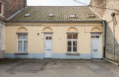 Facade of an old abandoned house built between two large houses Royalty Free Stock Photos