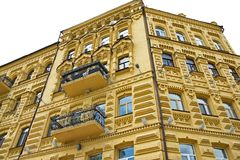 The facade of the old brick building. He facade of the old brick building painted yellow with balconies Stock Images