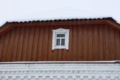 Brown wooden loft with a small window and a row of icicles on the roof under the snow royalty free stock photos