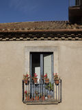 Facade of an old building with glazed windows. Small balcony and pots with red flowers Royalty Free Stock Photography
