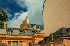 Facade of old buildings with roofs and windows in a sunny cloudy day at Paris. Stock Images
