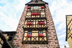Facade of old clock tower Riquewihr town. Travel to France - facade of old clock tower Riquewihr town in Alsace Wine Route Royalty Free Stock Images