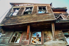 Facade of an old destroyed wooden building with broken windows Royalty Free Stock Photo