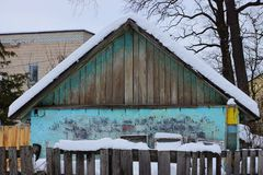 The facade of the old gray green rural barn of bricks and planks on the street behind a wooden fence in the snow. The facade of the old gray green rural barn of stock photos