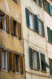 Facade of an old house in Florence with weathered wooden window shutters.  Stock Images