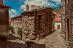 Facade of old house with stone wall between two cobblestone alleys. At Alvoco da Serra. A cute village clinging on a steep valley in the Serra da Estrela royalty free stock photography