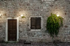 Facade of old house with a wooden door and a window, lit by two lanterns. Growing plants with foliage royalty free stock photos