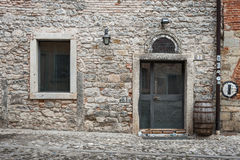 Facade of old Italian stone house with door and window, Cividale dei Friuli, May of 2015 Royalty Free Stock Photo