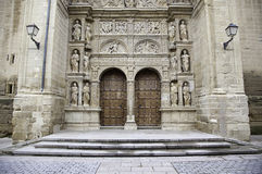 Facade of old medieval church. Detail of a wooden door and gothic sculptures, City Tours Royalty Free Stock Image