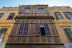 Facade of an old residential building with wooden ornate engraved wall, yellow painted wall, and violet painted wooden windows. In an old street, Old Cairo stock photos