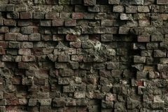 Facade of an old ruined building. Texture of a shattered grunge cement wall. The gray dirty dilapidated brick wall background stock images