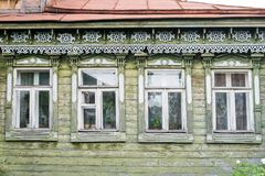 Facade of the old Russian village wooden house with carved ornaments elements. The facade of an old Russian rustic wooden house with carved wooden decorations stock images