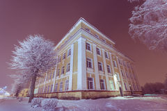 Facade of old school building. Winter landscape. Night. Stock Image