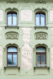 The facade of an old stone building. Windows and decorative stucco figures stock photo