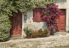 Facade of the old typical Italian house with red window, doors and flowers, Italy Stock Photo