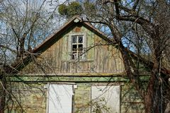 Facade of an old wooden house in a overgrown garden. Facade of an old wooden house with windows in the overgrown garden royalty free stock photo
