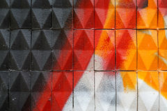 Facade with painted  ceramic triangular tiles. Dirty old facade with ceramic triangular tiles - painted with Stock Photo