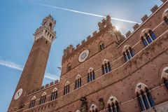 Facade of the Palazzo Comunale of Siena and Torre del Mangia backlighting stock photography