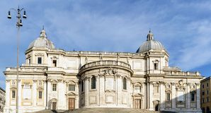 Facade of the papal Basilica called Santa Maria Maggiore, without people in sight and with a blue sky with very light clouds. In. The square called `Esquilino` stock images