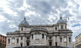 Facade of the papal Basilica called Santa Maria Maggiore, without people in sight and with a blue sky with very light clouds. In stock images