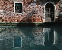 Facade of partially mossy old brick house with wooden vintage door on narrow canal in Venice, Italy. Royalty Free Stock Photos