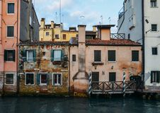 Facade of partially mossy old brick house with wooden vintage door on narrow canal in Venice, Italy.  stock photo