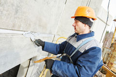 Facade plasterer sealing joint of building wall with putty mastic Royalty Free Stock Image