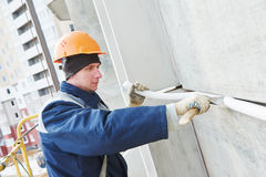Facade plasterer sealing joint of building wall with putty mastic Stock Image