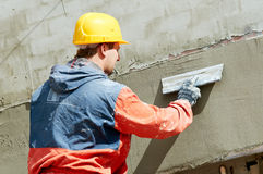 Facade Plasterer at work. Facade Plasterer at outdoor wall renovation decoration with float Royalty Free Stock Photography
