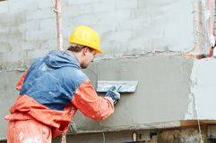 Facade work. builder plastering outside wall with putty knife float. Facade plastering work. builder smoothing plaster on outside wall with putty knife float royalty free stock image