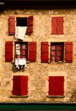 Facade with red wood shutters stock photography