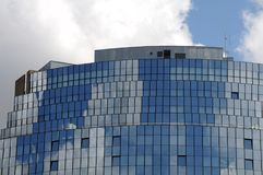 Facade reflecting blue sky and clouds. Curved glass facade at modern high building reflecting blue sky and white clouds Stock Photo