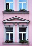 Facade of a residential building in vintage style. The Windows are decorated. With flowers. Pink wall color royalty free stock photography