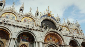 The facade of St. Mark`s Cathedral in Venice next to the Doge`s Palace. Popular place among tourists stock video footage