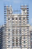Facade of a tall building in scaffolding. Royalty Free Stock Image