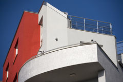 Facade and terrace modern building. In red and silver against the blue sky royalty free stock photo