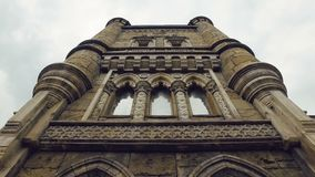Facade of tower of building in gothic-renaissance style, stained-glass windows, bas-reliefs. Tilt up panorama stock video footage