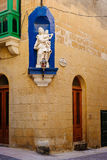 Facade of traditional maltese house. With niche at the corner decorated with statue of Our Lady with Child, Rabat, Gozo Stock Images