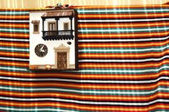 Facade of a traditional miniature house hanging on the wall with a colorful cloth underneath. Colorful image with a facade of a traditional miniature house stock photo