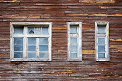 Facade of a tumbledown wooden house. With broken window Stock Images
